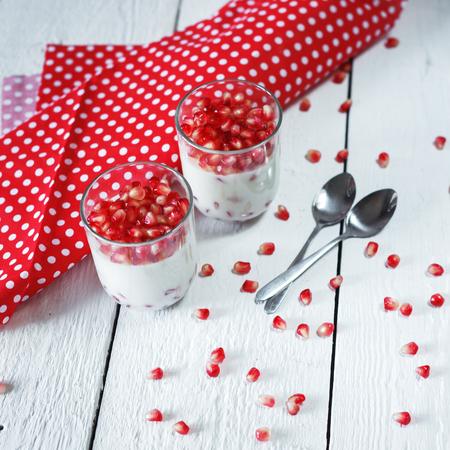 pannacotta: Delicious dessert  pannacotta with fresh pomegranate seeds in a glass jar on white background Stock Photo