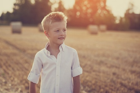 kinder spielen: Portrait eines glücklichen Kindes in den sonnigen Tag in einem Feld, getönten Bild