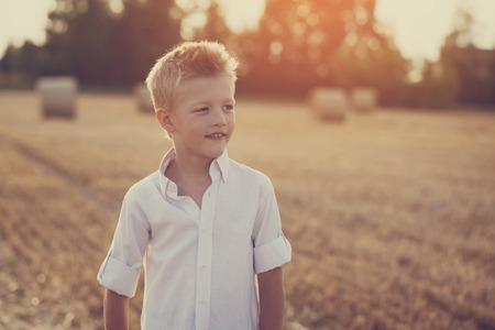 niños rubios: retrato de un niño feliz en el día soleado en un campo, imagen de tonos Foto de archivo