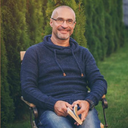 The mature senior man reading novel in country home garden, toning image Standard-Bild