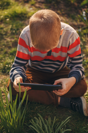absorbed: Little kid absorbed into his tablet
