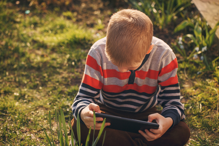 absorbed: Little kid absorbed into his tablet, outdoor Stock Photo