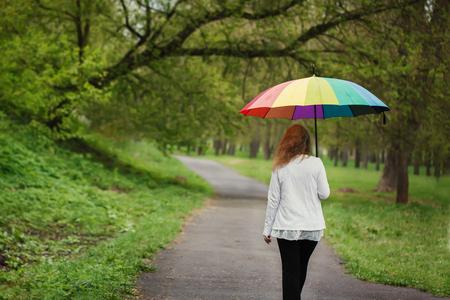 Vista trasera de la joven womanl bajo un paraguas brillante, caminar bajo la lluvia