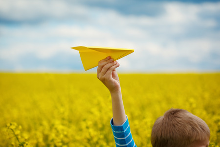 airplane: Paper airplane in children hands on yellow background and blue sky in coudy day