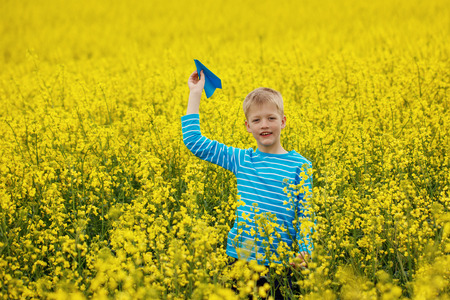 Young Boy with paper Plane against blue sky and Yellow Field Flowers