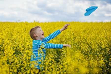 Happy boy started the blue paper aiplane in the sky over the yellow blossoming field in a sunny day Standard-Bild
