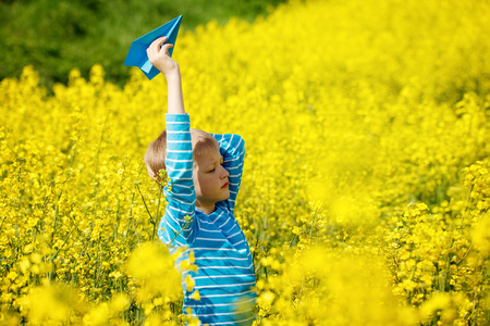 yellow paper: Happy boy leaning and throwing  blue paper airplane on bright sunny day in the yellow field fowers