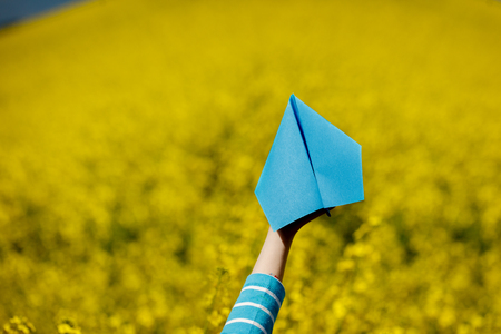 Paper airplane in children hands on yellow background