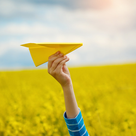 Paper airplane in children hands on yellow background and blue sky in coudy day