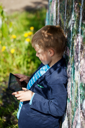 absorbed: Little kid  absorbed into his tablet for educating and playing.Boy standing near a wall  graffiti.