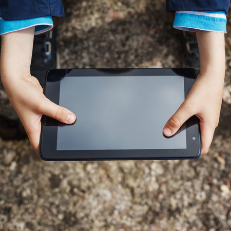 electronic tablet: close up  kids hands multitasking  using tablet, laptop for playing or education