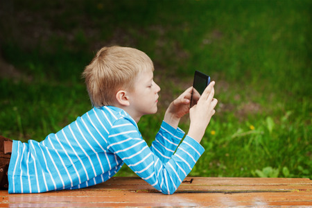 blonde boy: Cute boy lying in park and using tablet pc for play