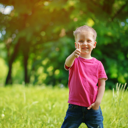 outside: Happy little  boy  in the park. On warm sunny   summer day. Kid  smiling, shows a class Stock Photo