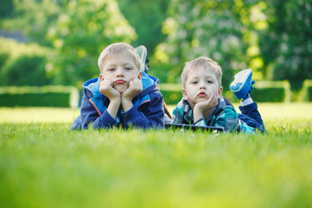 suny: Siblings using a tablet, yingon grass in the park in suny day
