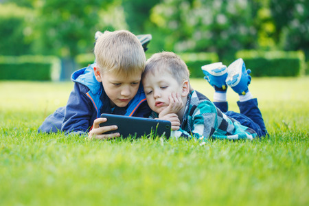 digital device: Siblings using a tablet, yingon grass in the park in suny day