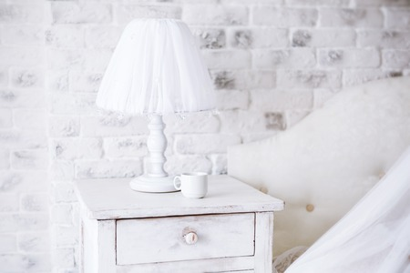 bedside lamp: Interior Home. White lamp and  cup of coffee on a bedside table in a bedroom in early  morning.