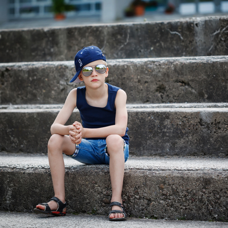 little one: Fashionable little boy in sunglasses and cap siting on stone steps. Childhood.  Summertime. Square.