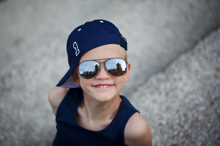 smiing: Smiing Portrait of Fashionable little boy in sunglasses and cap. Childhood.  Summertime.