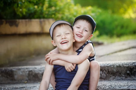 love hug: Two adorable  sibling boys hugging and having fun outdoors. Cute friends playing together on sunny warm summer day. Brother love. Stock Photo