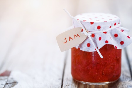 Fresh strawberry homemade jam in jar on white wood background. healthy organic and vegan food.