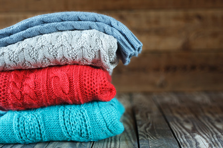 Stack of knitted sweaters on wooden background.