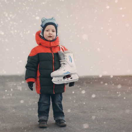 figureskating: cute little boy  holds the skates wearing warm winter clothes  going ice skating, snow