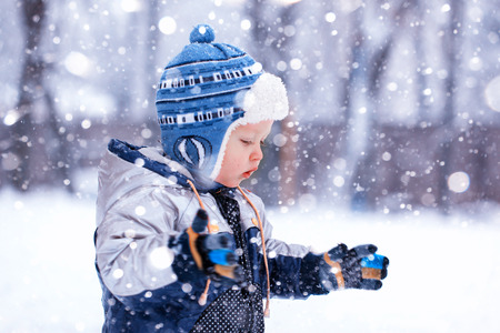 the cute little boy catches snowflakes in the frosty winter afternoon Zdjęcie Seryjne