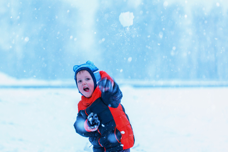 palle di neve: cute little boy playing outside and throwing snowballs in winter