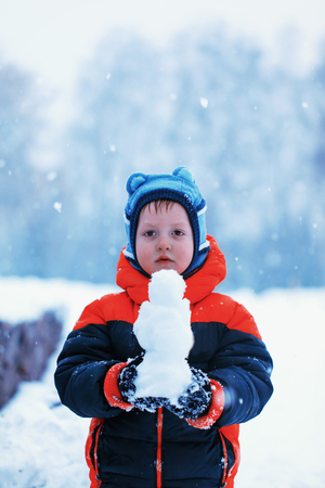 winterday: Half-length portrait of boy who stands in winter park holding snowman in his hands in winterday