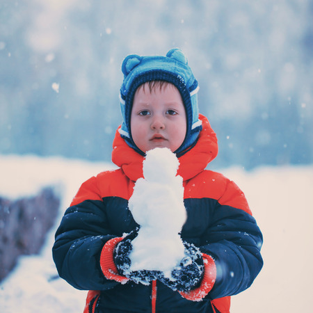 winterday: Half-length portrait of boy who stands in winter park holding snowman in his hands in winterday, square