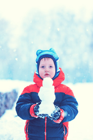 winterday: Half-length portrait of boy who stands in winter park holding snowman in his hands in winterday, toned image