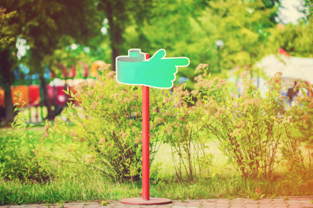 channelize: Notice board, green blank plate for text in the park on natural background