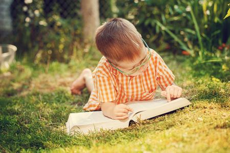 Portrait  Happy little boy holding a big book  on his first day to school or nursery. Outdoors, Back to school concept