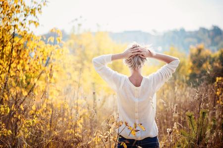 pensando: Rapariga feliz desfrutando da beleza do dia ensolarado do outono na grama alta em um parque do outono. Vista de uma volta.