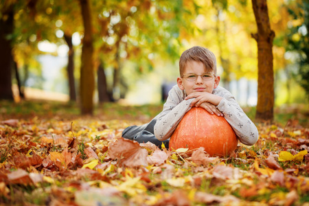 Cute little boy  leaning on a pumpkin, autumn time