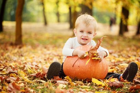 Little toddler boy having fun with orange pumplkin in autumn park.