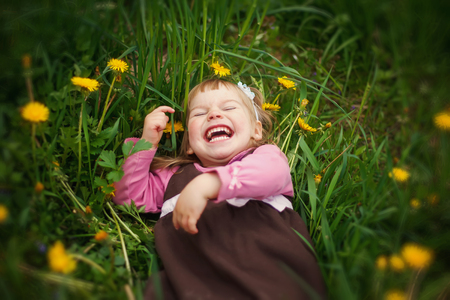 laughing: the little happy girl lies in a grass and laughs in the sunny day