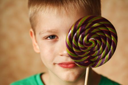 big behind: The little lovely boy hides behind big sweet sugar candy