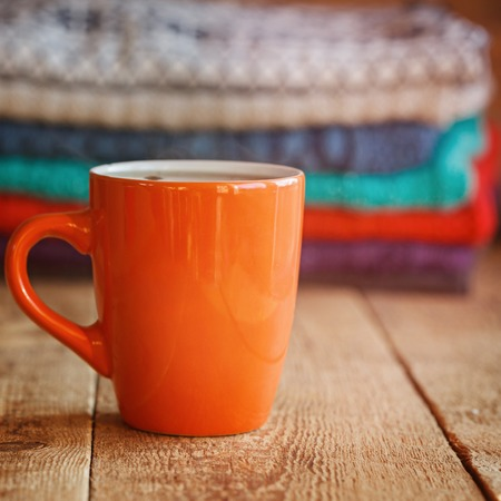red cardigan: Red Cup of teaor coffee  with stack of  knitted sweaters on a wooden table