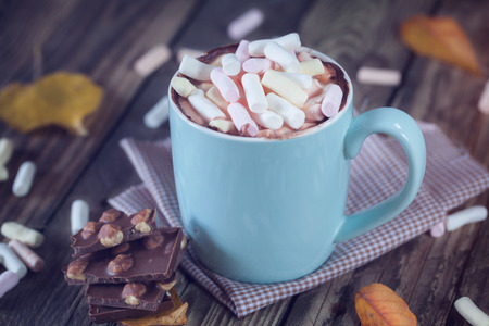 Mug filled with hot chocolate and marshmallow, with  chocolate