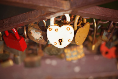 closed lock: beautiful white heart-shaped padlock locked on iron chain, romance concept