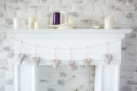 romaans: Handgemaakte textiel witte harten opknoping op een koord op witte bakstenen muur, rustieke stijl. Romantiek consept.