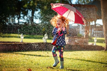 chicas sonriendo: Niña muy feliz con el paraguas que juegan en la lluvia. Los niños juegan al aire libre por el tiempo lluvioso en el otoño.