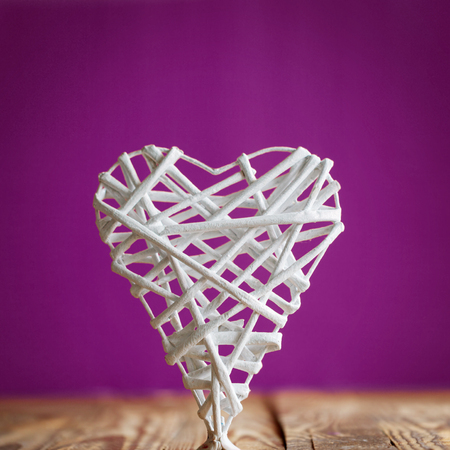 home accent: White heart handmade of rods on a purple background. Valentines Day. Stock Photo