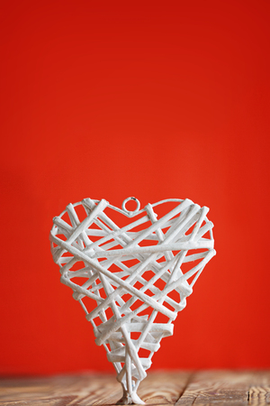 home accent: White heart handmade of rods  on a red background. Valentines Day. Stock Photo