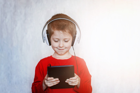 early education: little boy with headset using touch pad, early education and learning