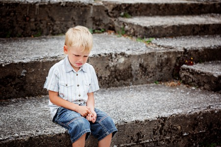 Little Boy crying  sitting on stone steps in park. Loneliness, melancholy, stress