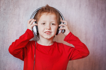 keep your hands: Cute portrait boy in headphones enjoys music, Keep your hands on the headphones.