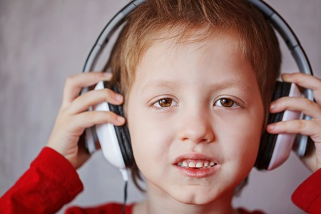 keep your hands: Closeup portrait boy in headphones enjoys music, Keep your hands on the headphones. Stock Photo