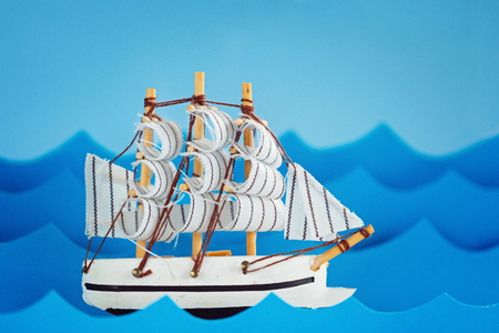 warm things: White Ship on blue wave with paper. Travel and adventure concept.